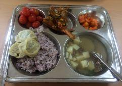 cherry tomatoes, cooked fish, kimchi radish, mandu (dumplings) beef and potato soup, purple rice