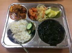 Pork in sauce with rice cakes, kimchi radish, bean sprouts, melon, rice, seaweed soup
