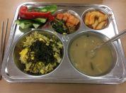 fresh vegetables, kimchi radish, tteokpoki (rice cake) mixed rice with vegetables, egg, tuna, seaweed mushroom soup