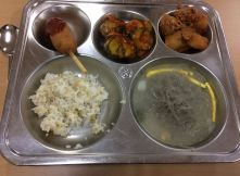 corn dog with ketchup, kimchi with vegetables zucchini, fish and potatoes, rice, soup with rice noodles and egg and beef